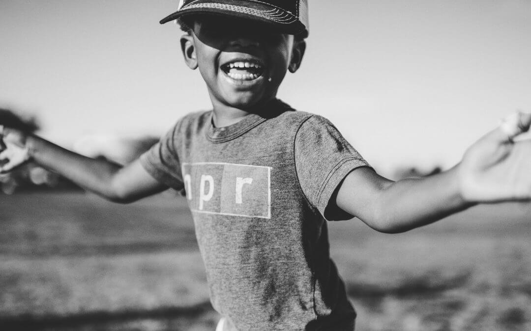 A young boy wearing a ball cap smiles for the camera as he enjoys outdoor fun at an Ottawa summer camp.