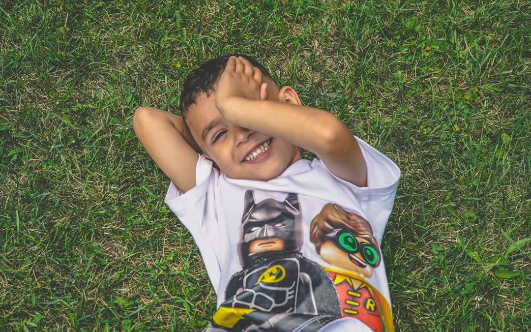 Child smiling sitting on the grass wearing a Lego superhero shirt.