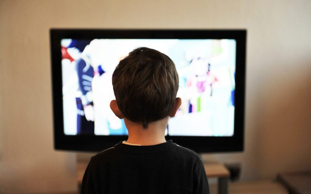 A young child stares at a TV screen.