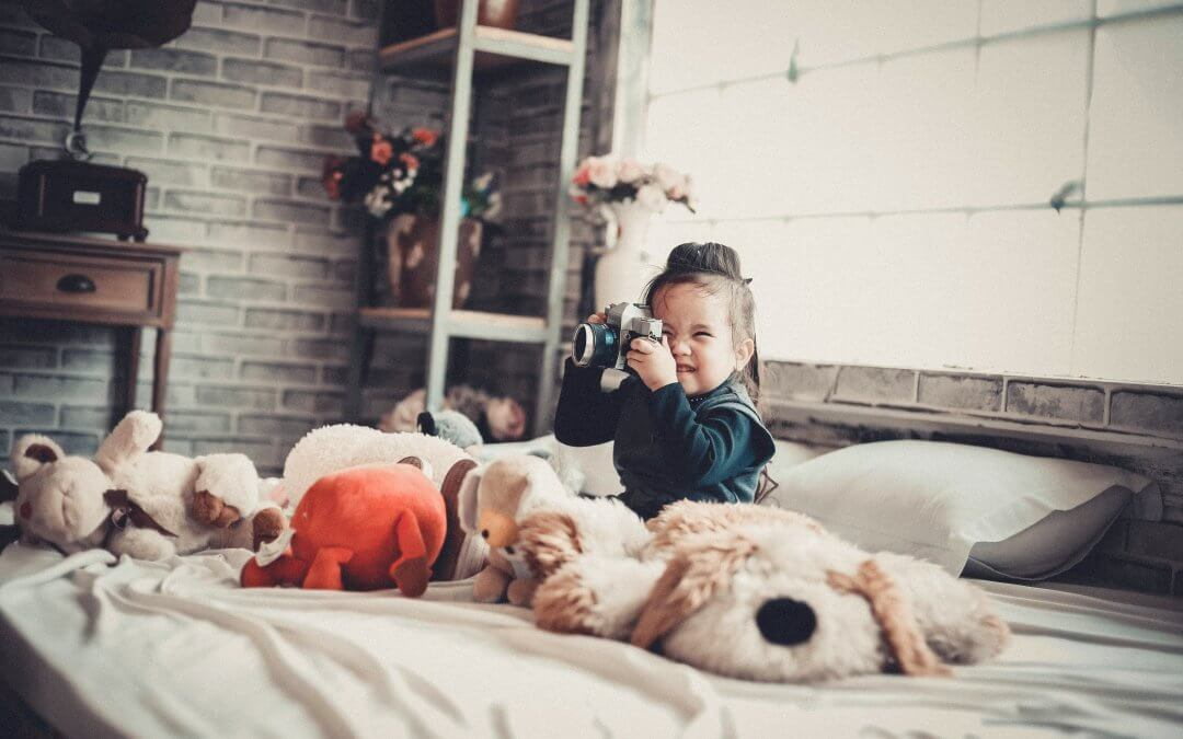 A young girl smiles as she takes a photo on a camera, surrounded by stuffed toys.