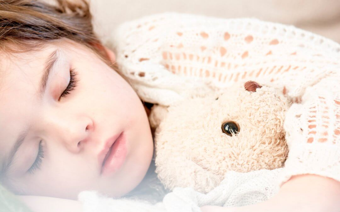 Young child sleeps while snuggling with her teddy bear
