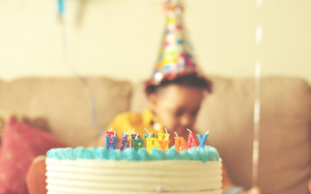 A child with a party hat sits behind a birthday cake.