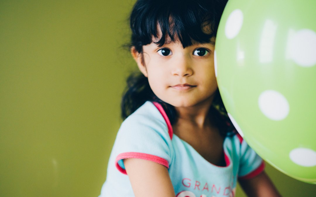 A young girl sits calmly behind a balloon.