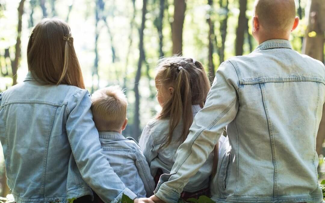 Family of four wearing jean jackets sit on a fallen log in the bright forest