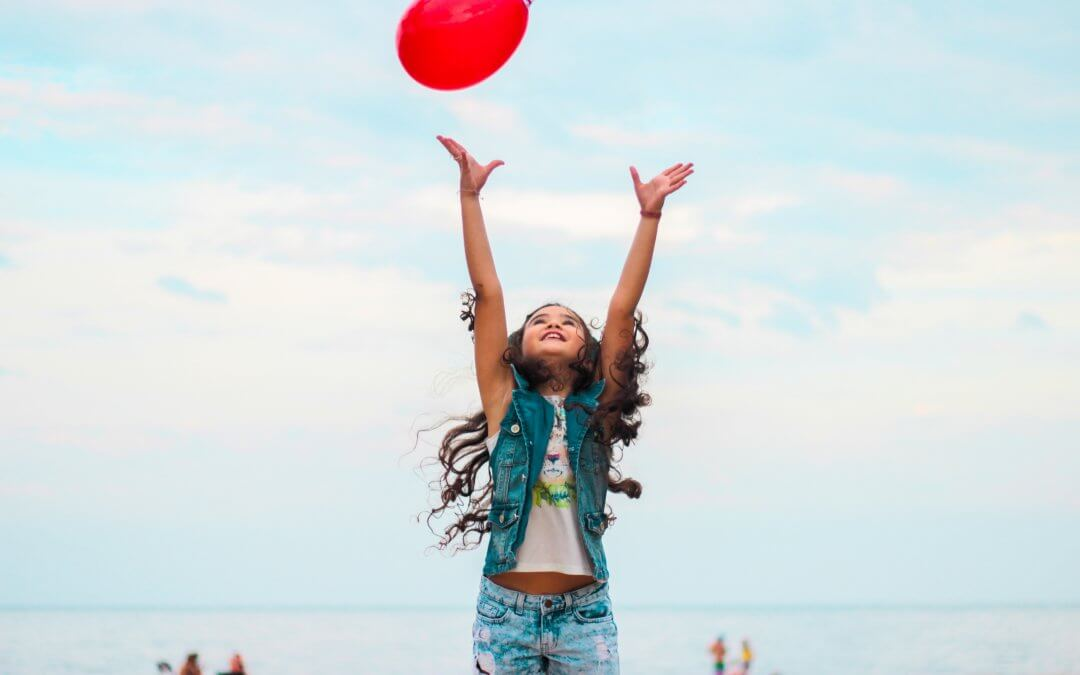 Young girl plays by the beach with a red balloon