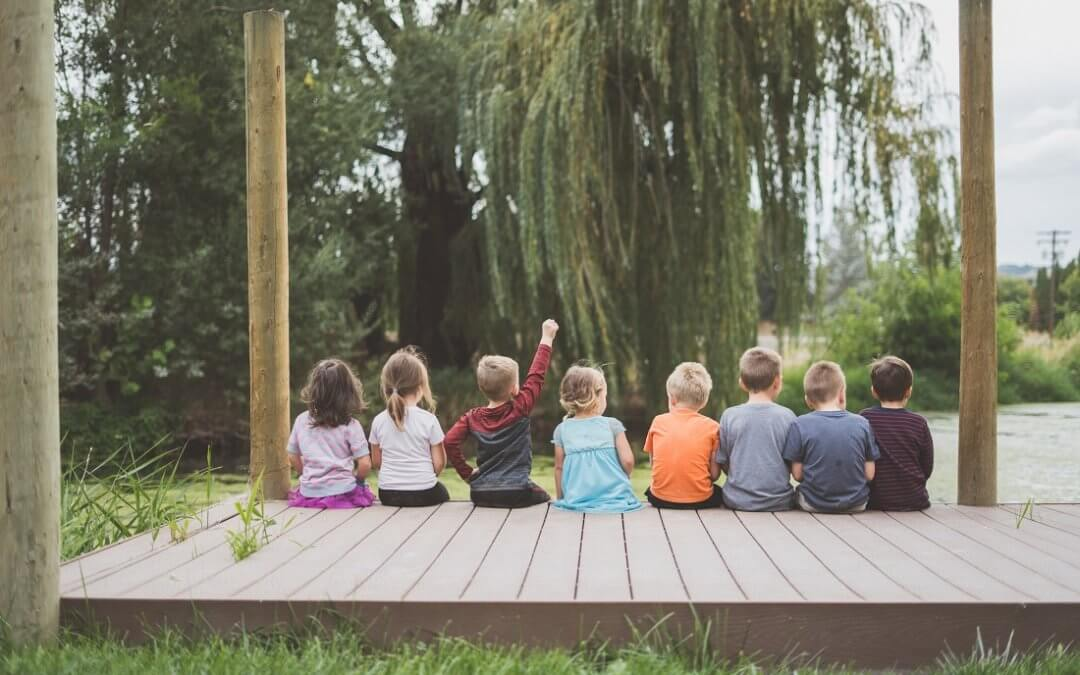 Eight children sit side-by-side on a porch outside