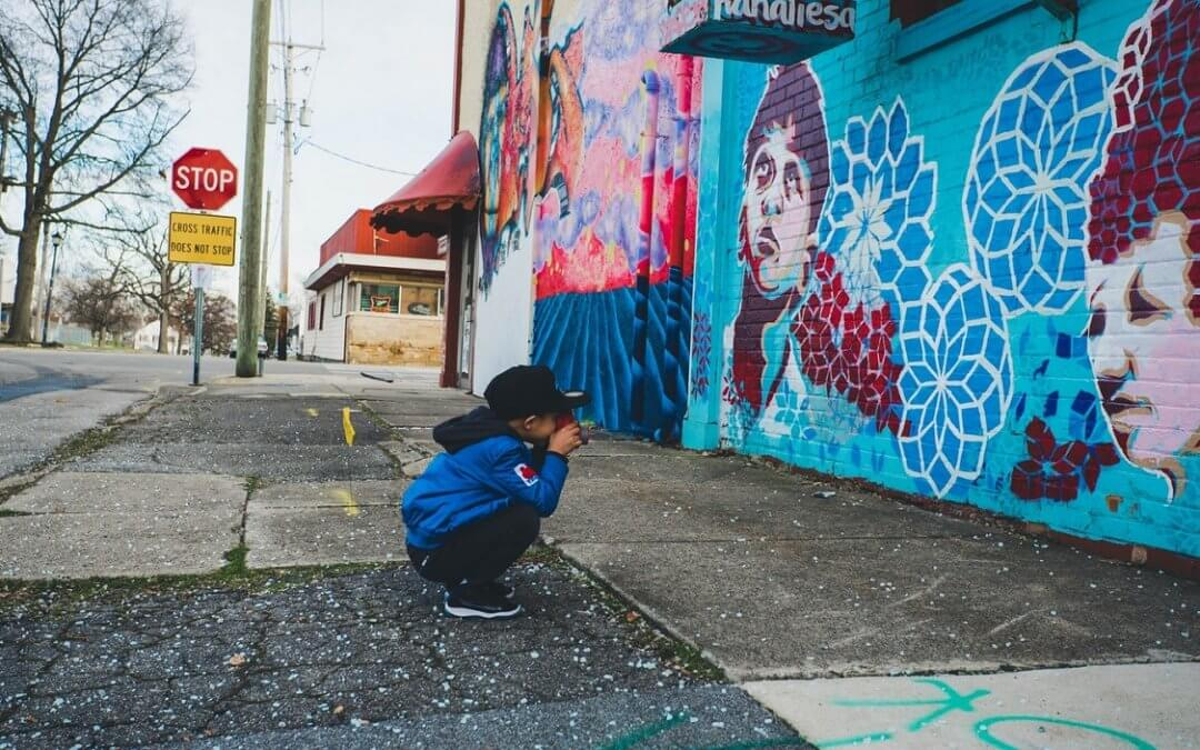 child crouches down to take a photo of a mural in an urban area