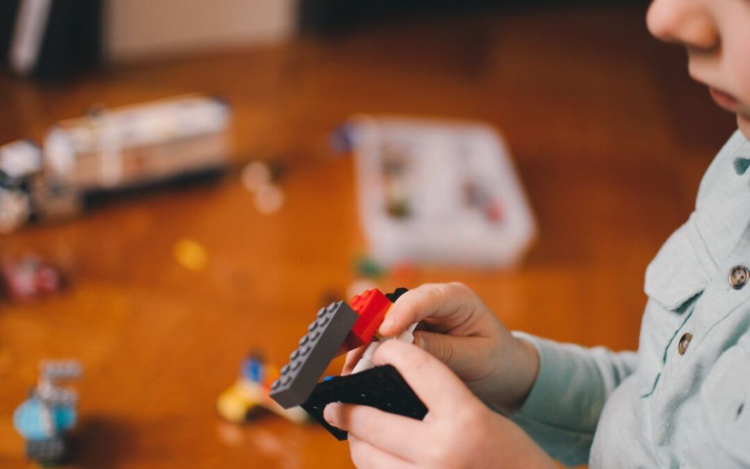 Young boy plays with Lego at home