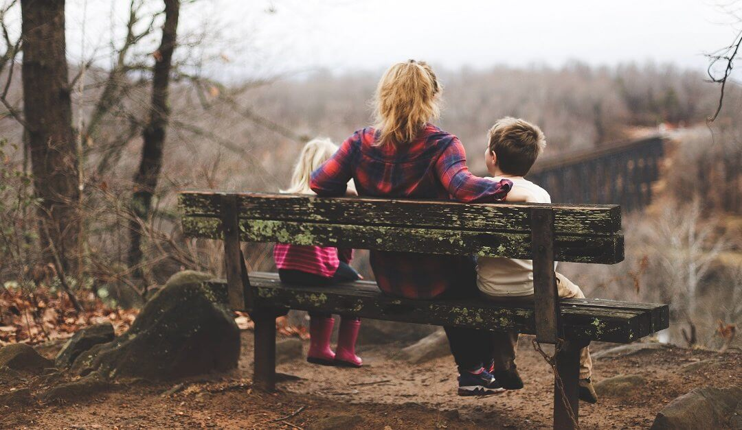 Mother and her two kids sit on a bench in the woods in the fall