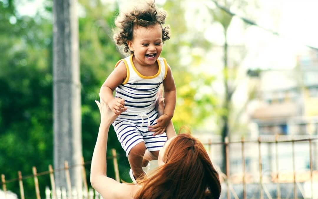 mother plays with her laughing child in the park