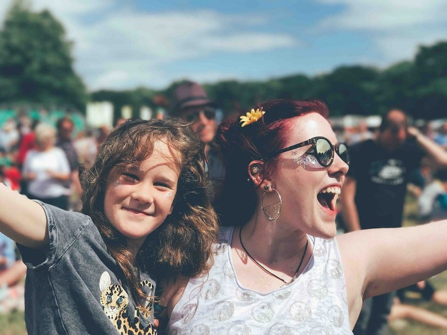 Mother and daughter laugh at a festival with paint on their faces