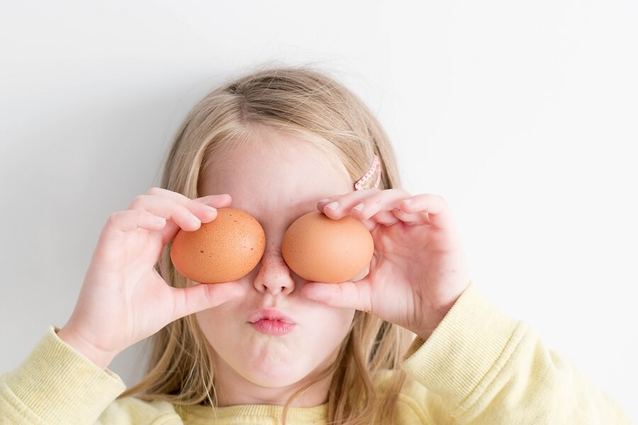 Young girl covers her eyes with two brown eggs