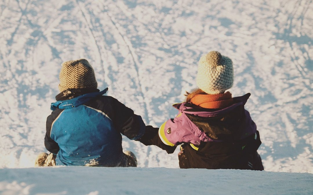 Two young toddlers hold hands on the top of a snowy hill