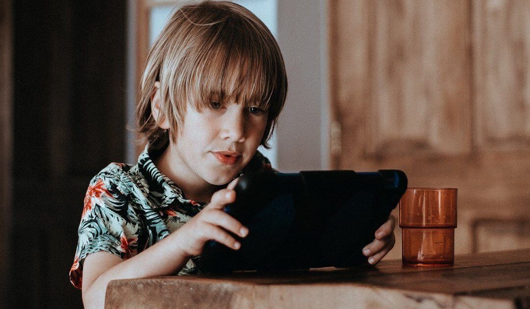 Young boy learns and plays on tablet at the table