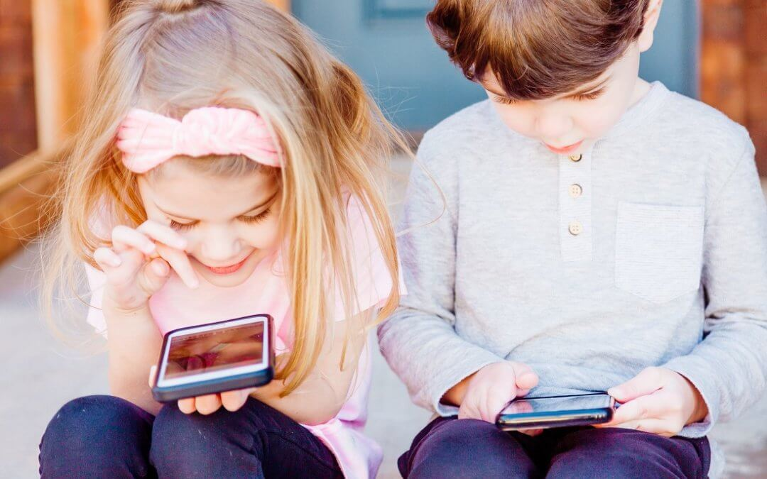 Two young children sit on a stoop and stare into their phones