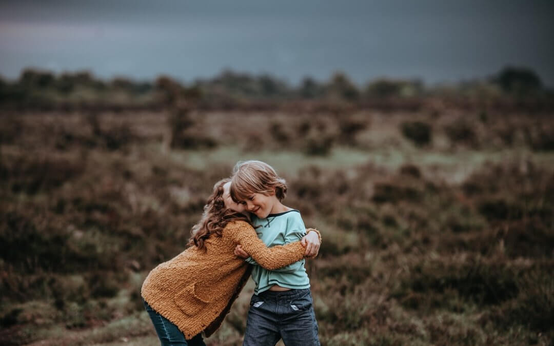two siblings hugging and smiling