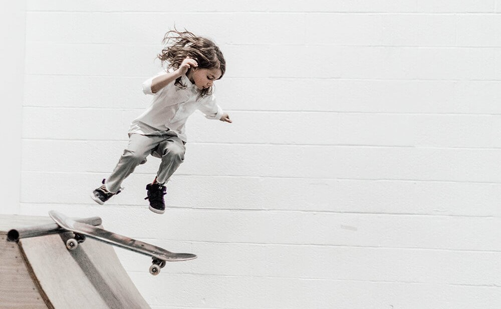 A young girl drops into a halfpipe on a skateboard.