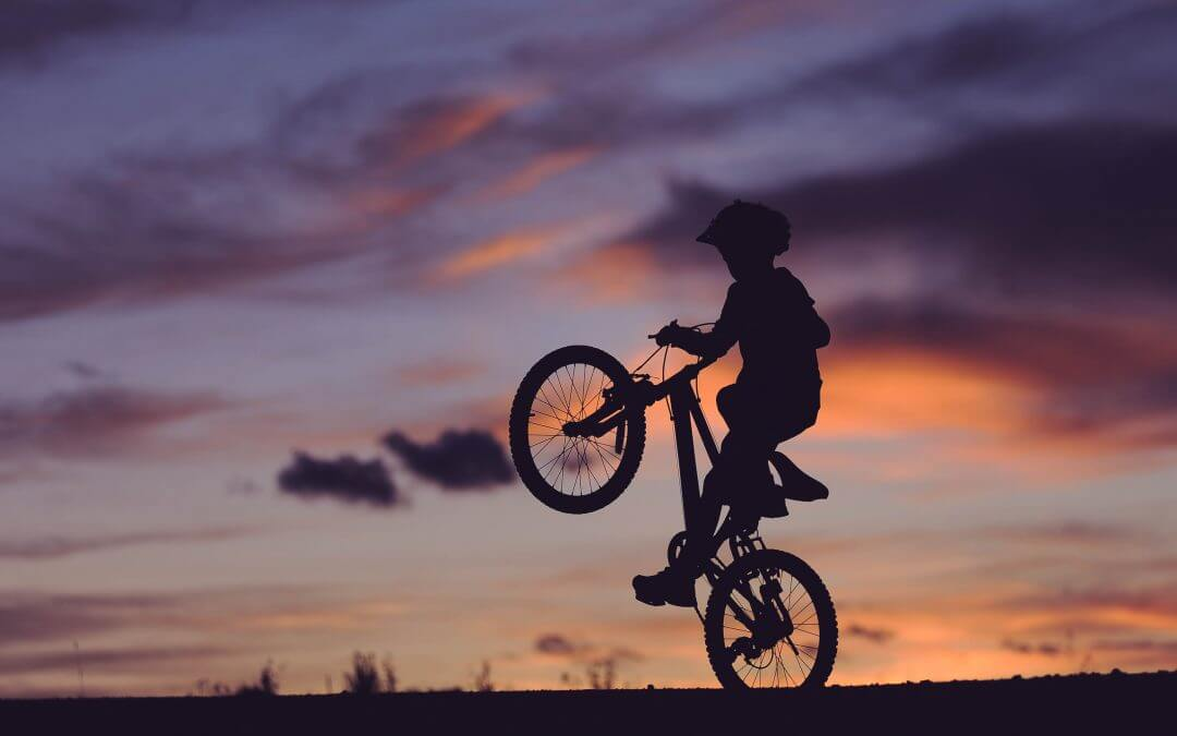 Silhouette of child playing on their bike at dusk in a field.
