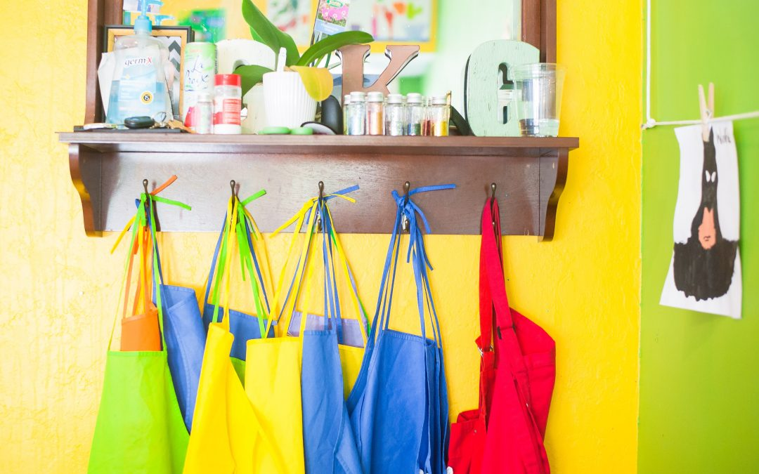 Colourful canvas aprons hang on a shelf in a daycare with bright walls