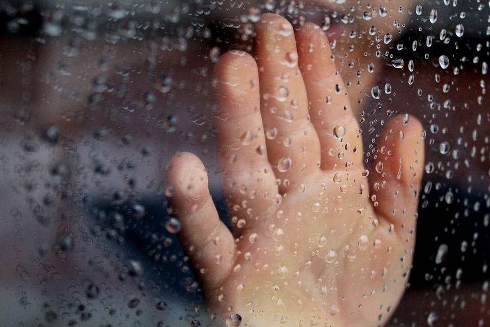 kid at window on rainy day