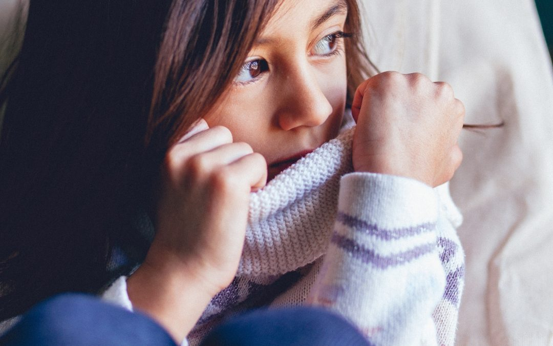 A young girl anxiously pulls her sweater over the lower half of her face.