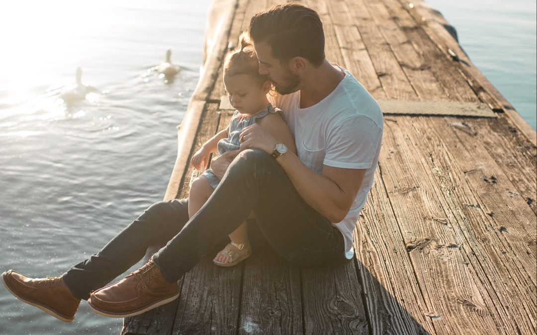 A father holds his sulking daughter close, sitting on a wood dock in the sun.