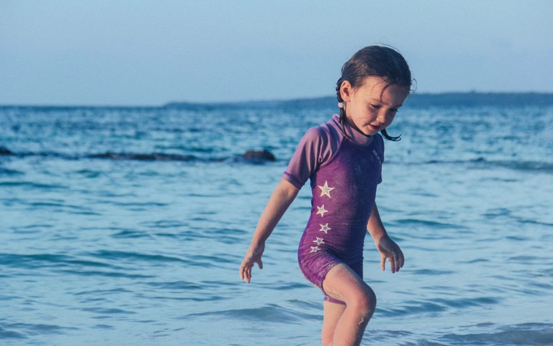 A young girl in a purple swimsuit with gold stars plays on a beach during an Ottawa summer camp stay.