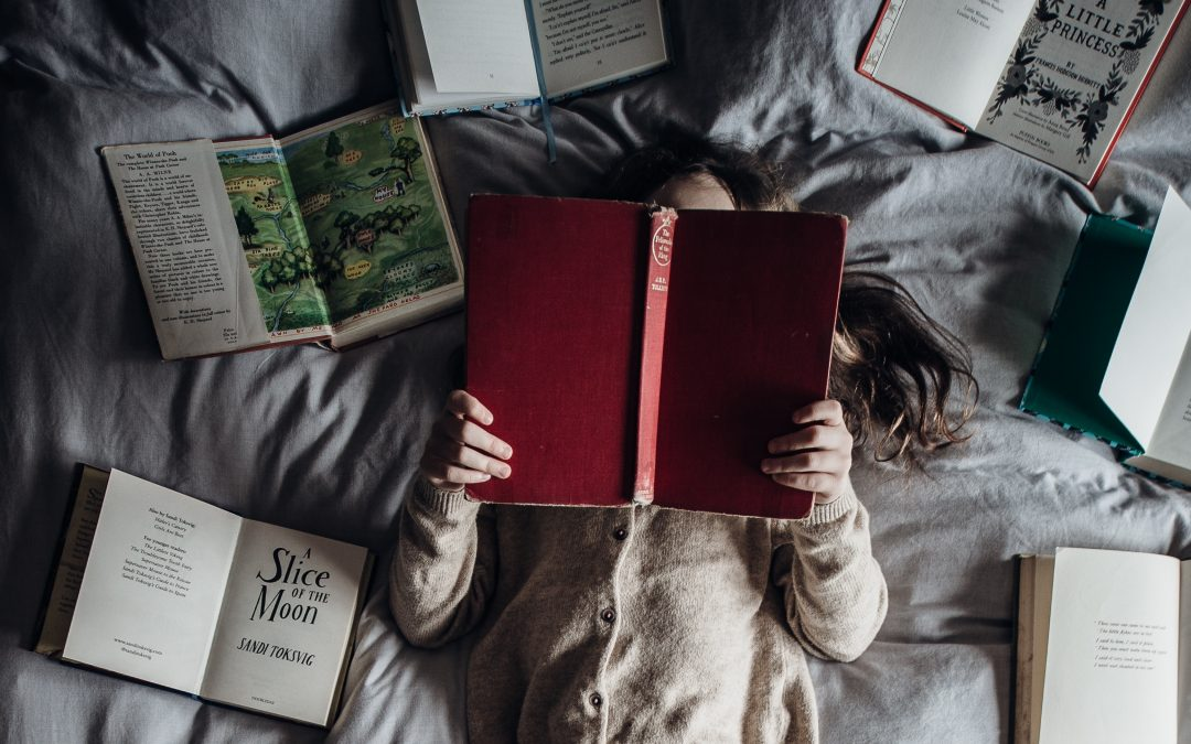 A young girl in a gray sweater sits back on a bed, reading a red novel with many other books open around her.