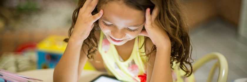 A young girl stares happily into her iPad watching a show at daycare.