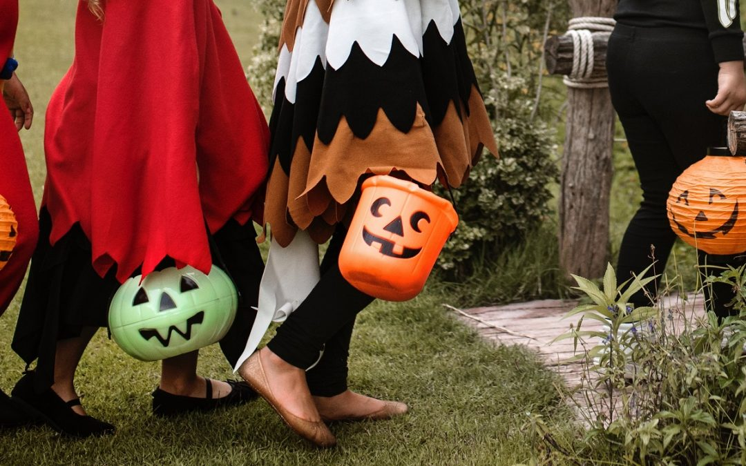 Children trick-or-treating with their candy buckets and costumes on