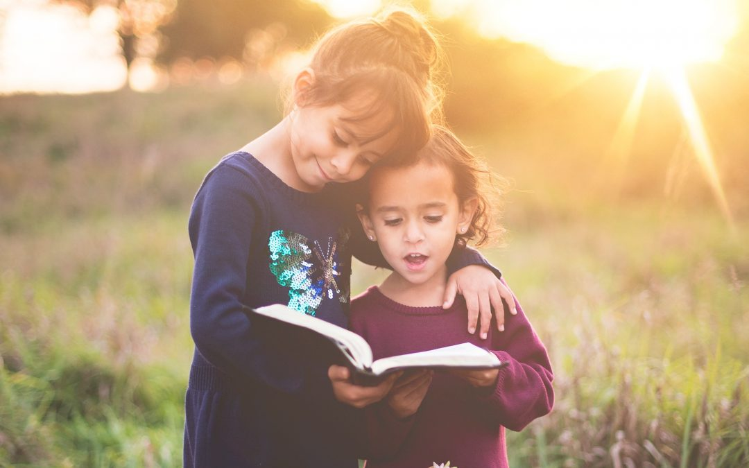 Two children hug and read a book together outside