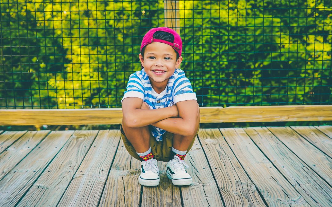 Young boy wearing red ball cap smiles and crouches on deck in front of trees
