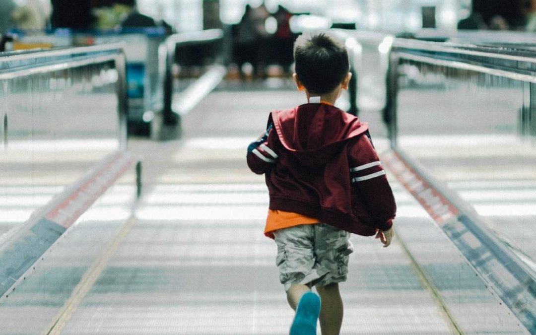 A child runs down a moving walkway in an airport.