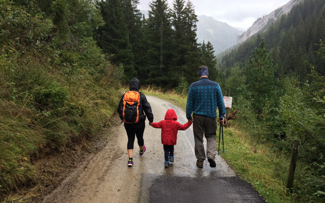 A family of three hold hands as they hike in the forest in the rain